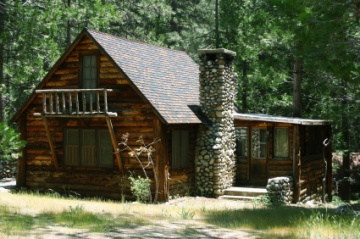 Log cabin in the woods with a stone chimney