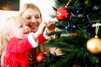 Mom and daughter decorate a Christmas tree