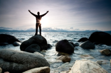 Man standing on a rock, reaching to the sky