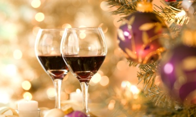 Two glass of red wine beside a Christmas tree