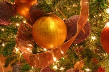 A  gold ornament on a Christmas tree