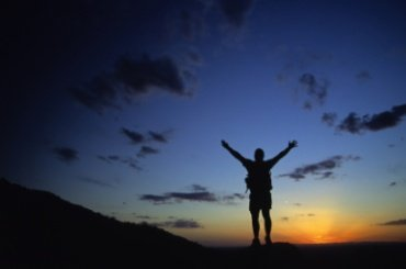 Man lifting his arms to the twilight sky