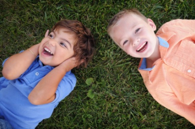 Boys laying and laughing on the grass